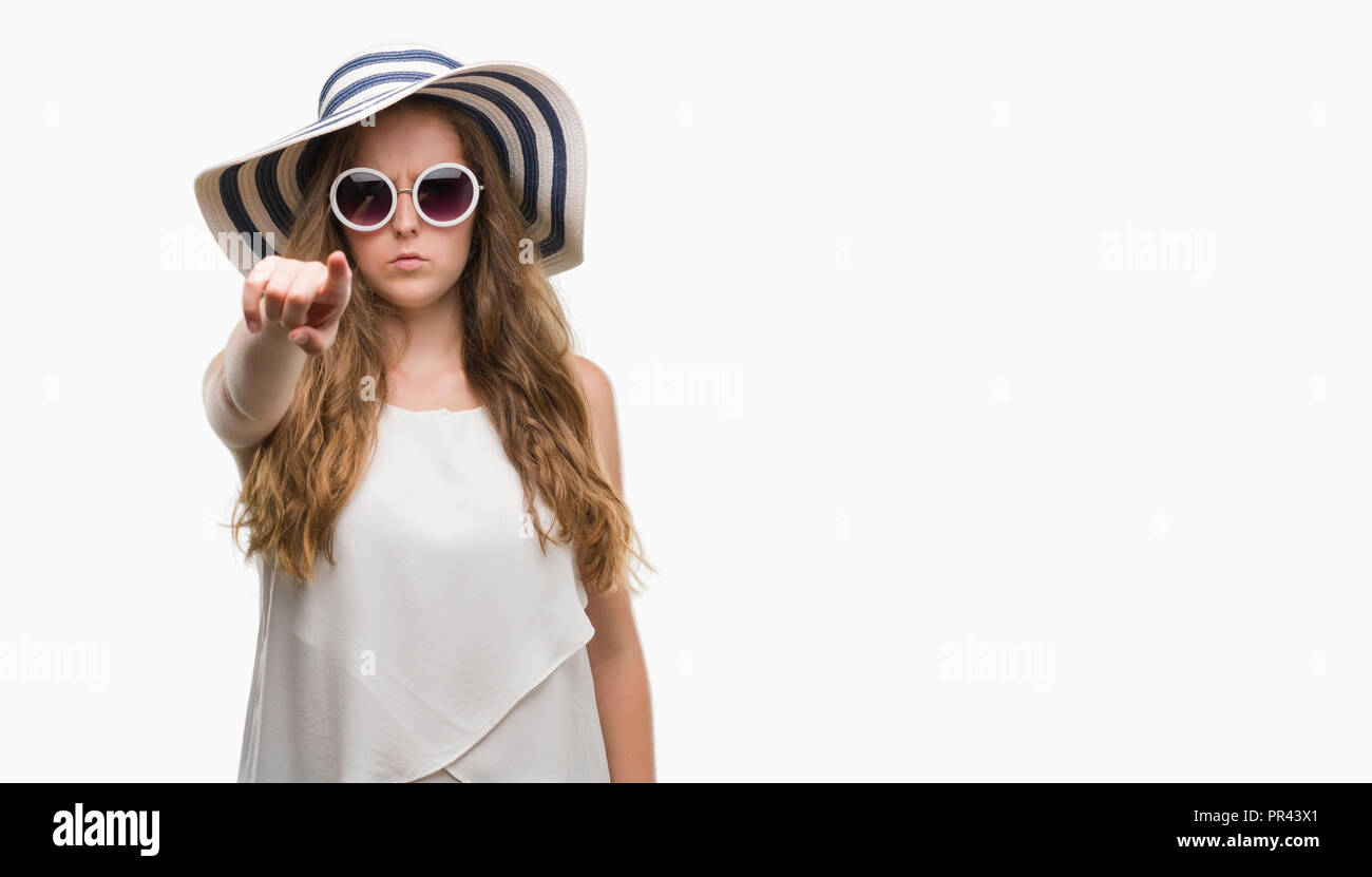 Young blonde woman wearing sunglasses and summer hat pointing with finger to the camera and to you, hand sign, positive and confident gesture from the - Stock Image