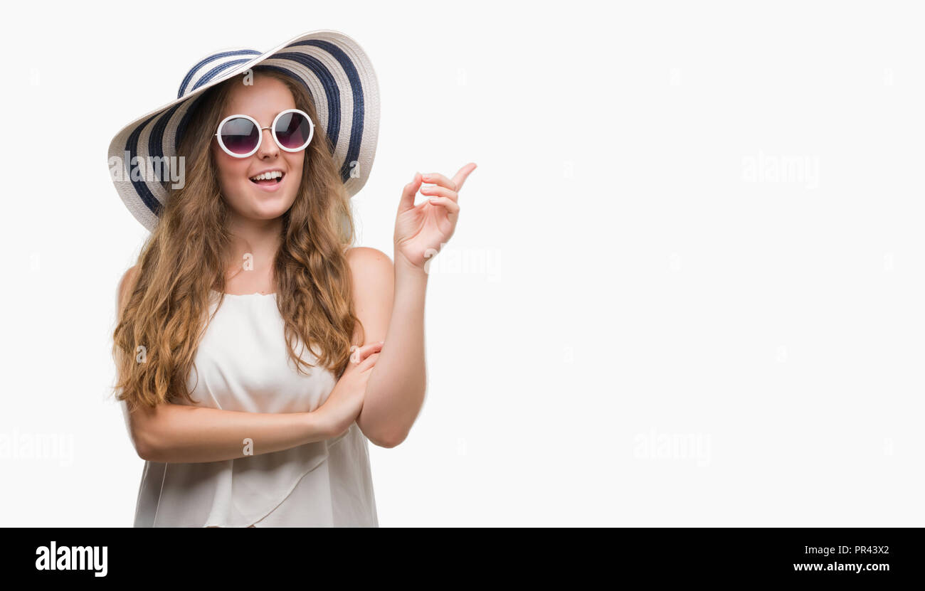 Young blonde woman wearing sunglasses and summer hat very happy pointing with hand and finger to the side - Stock Image
