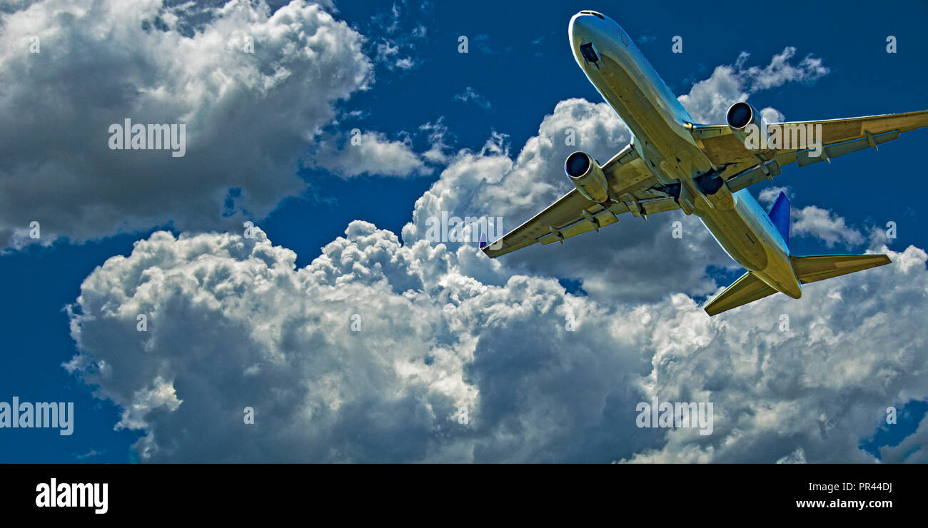 An action skyscape view of a commercial passenger jet aircraft  flying closeup in vibrant blue sky, with  developed white coloured cumulonimbus cloud. - Stock Image