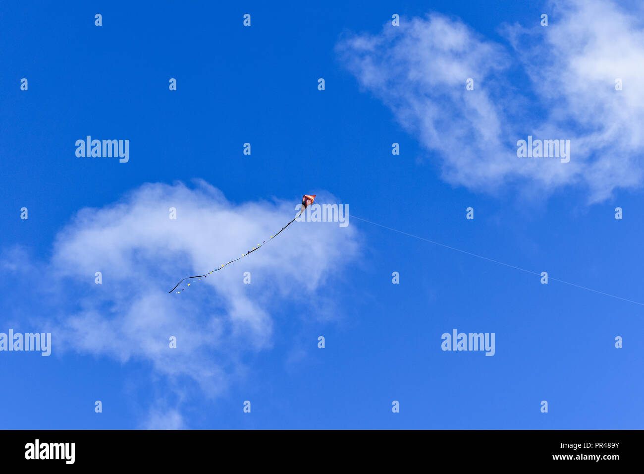 A red kite flying against a blue sky. Child's play. - Stock Image