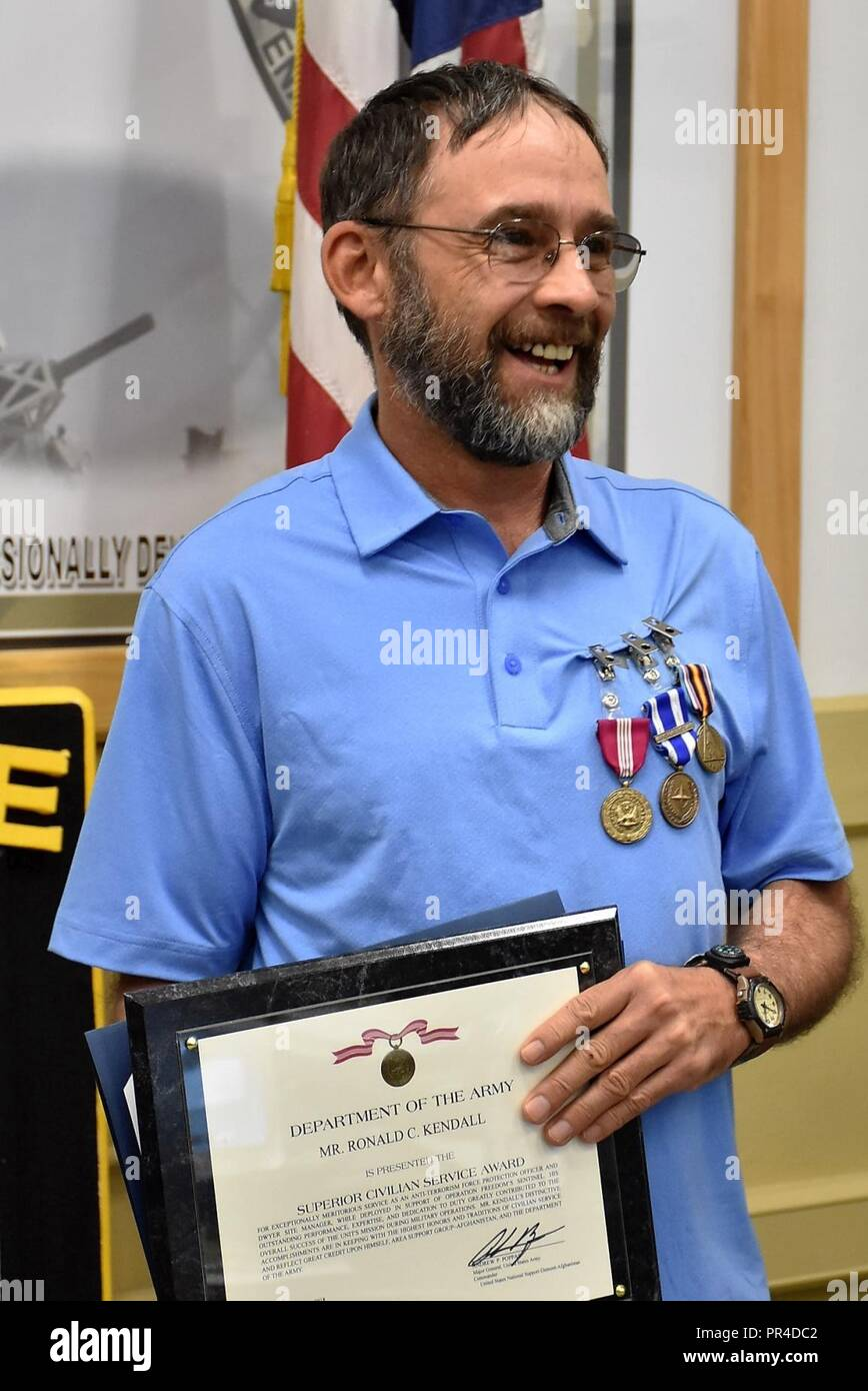 Department of the Army Civilian Ron Kendall was awarded the Superior Civilian Service Medal, NATO Medal and Global War on Terrorism Service Medal Sept. 10 for exceptional service to Area Support Group-Afghanistan (ASG-A). ASG-A Commander Col. Jacob Peterson presented Kendall the awards at the organization's headquarters on Bagram Air Field.     Kendall was assigned to ASG-A on a one-year deployment through the Department of Defense Expeditionary Civilians Program, which deploys personnel to support military operations. Before redeploying to the United States in September 2018, Kendall served a - Stock Image