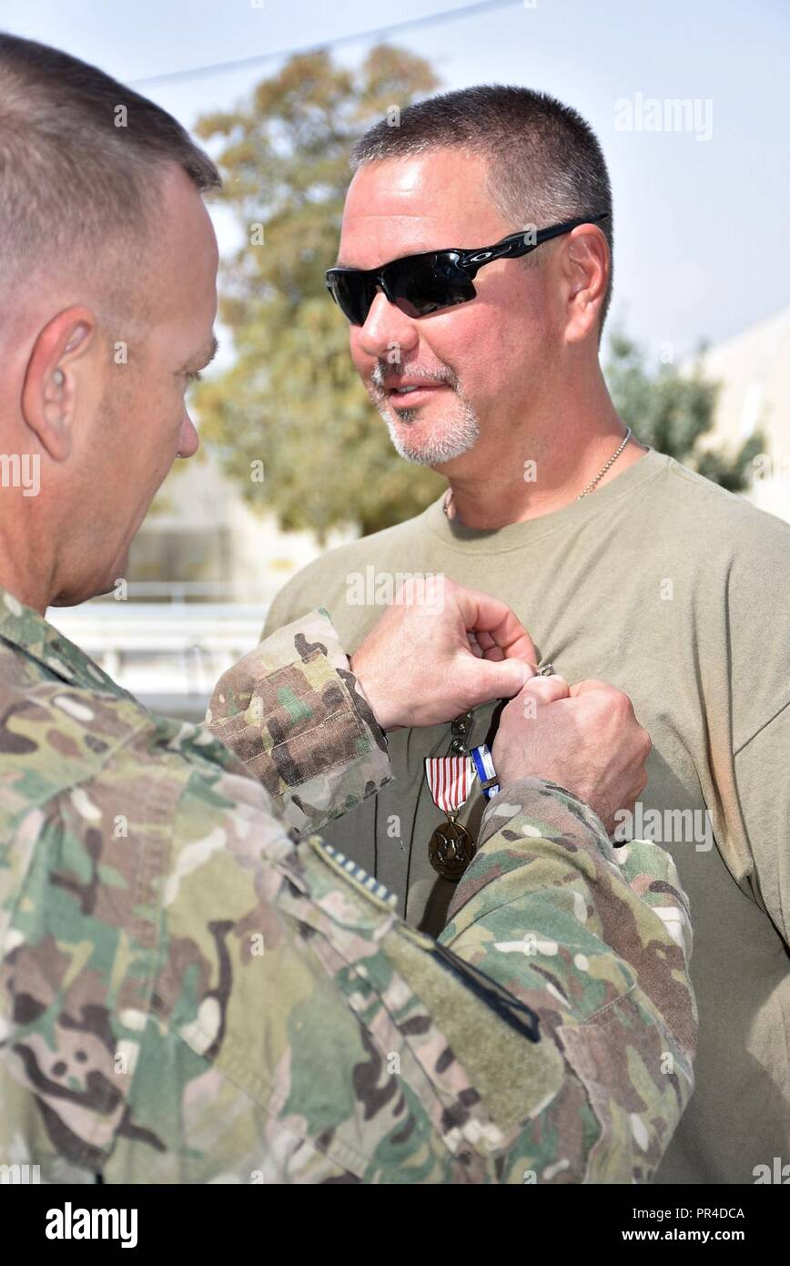 (From left) Area Support Group - Afghanistan (ASG-A) Commander Col. Jacob Peterson presents Department of the Navy Civilian Jonathan Covington the Outstanding Civilian Service Medal, NATO Medal and Global War on Terrorism Service Medal Sept. 6 for exceptional service to ASG-A.     Covington was assigned to ASG-A on a one-year deployment through the Department of Defense Expeditionary Civilians Program, which deploys personnel to support military operations. Before redeploying to the United States in September 2018, Covington served as the site manager of Forward Operating Base (FOB) Lightning, - Stock Image