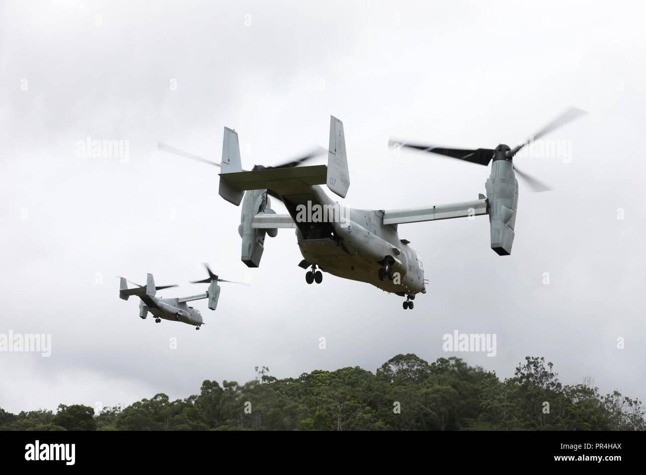 MV-22 Osprey aircraft assigned to Marine Medium Tiltrotor Squadron 363 (VMM-363), takeoff during a confined area landing exercise on near the Kahuku Training Area, Sept. 13, 2018. The training provided an opportunity for pilots and crew chiefs to improve their proficiency and experience in flying around a tropical environment. Stock Photo