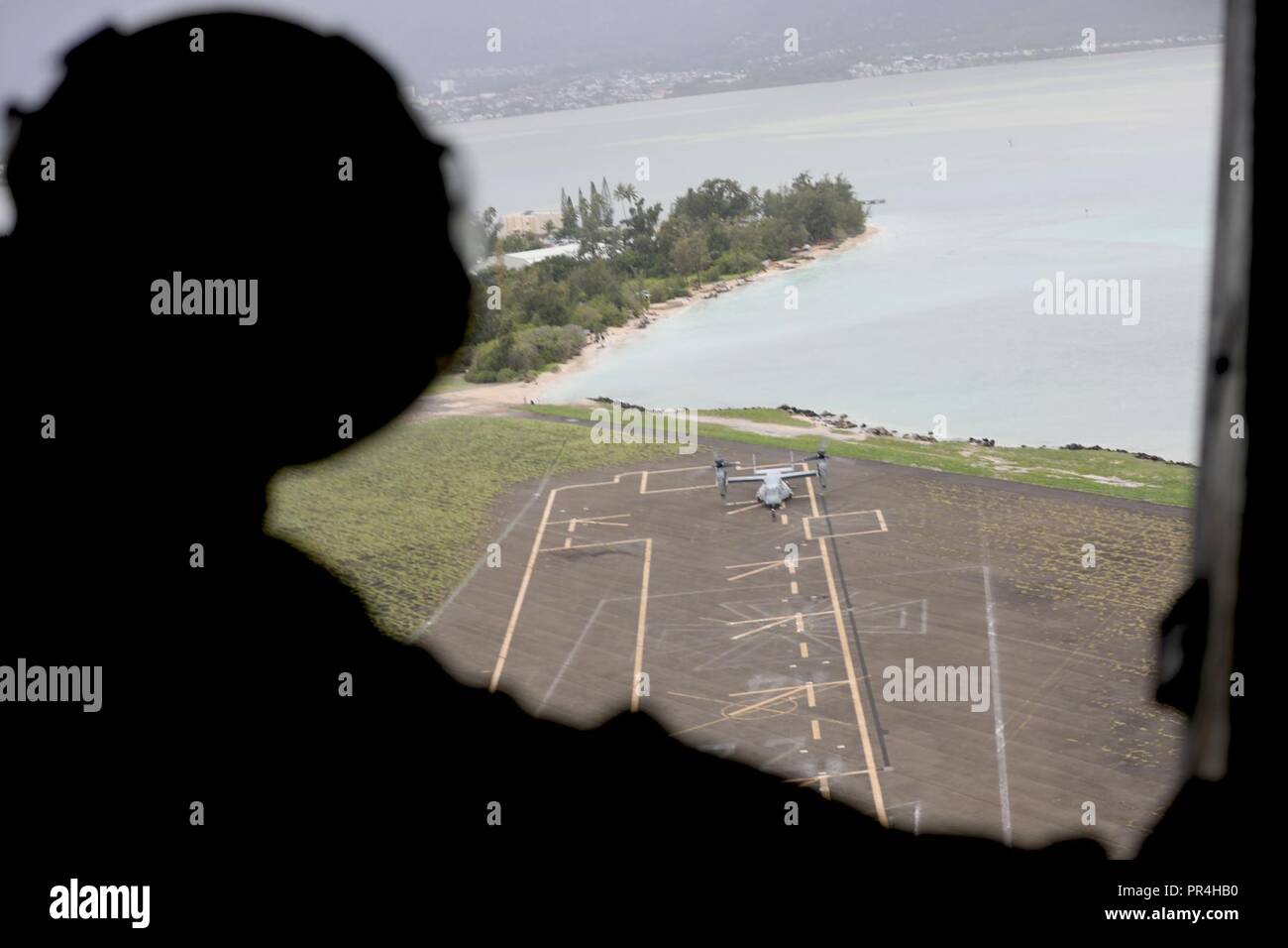 A U.S. Marine Corps MV-22 Osprey crewchief, observes a second Osprey aircraft touch down at Landing Zone Westfield, both assigned to Marine Medium Tiltrotor Squadron 363 (VMM-363), during confined area landing exercises on Marine Corps Base Hawaii, Sept. 13, 2018. The training provided an opportunity for pilots and crew chiefs to improve their proficiency and experience in flying around a tropical environment. Stock Photo