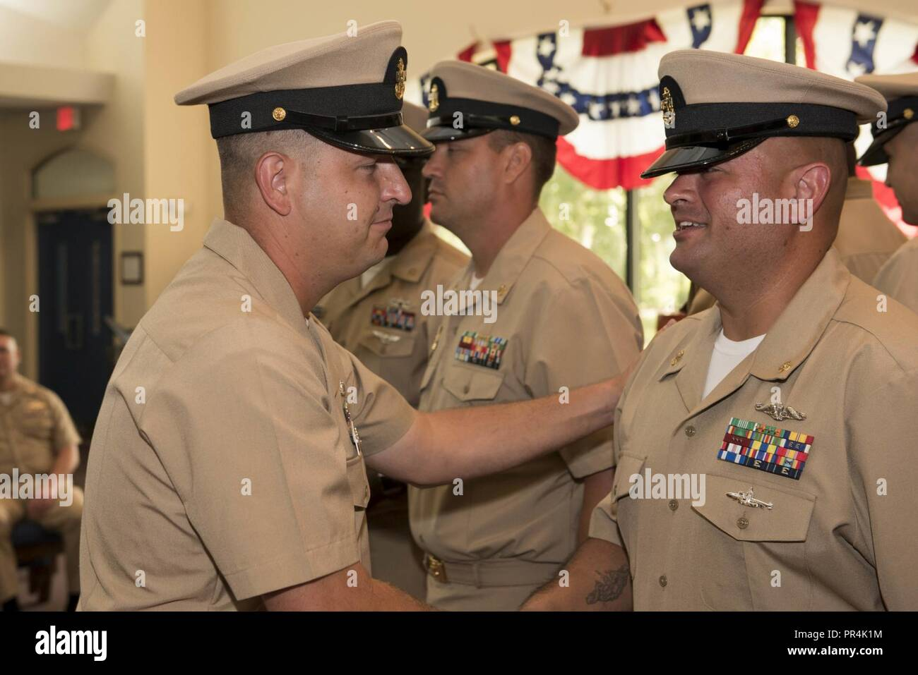 KINGS BAY, Georgia (Sept. 14, 2018) Chief Culinary Specialist (Submarines) John Nordman is congratulated by his sponsor during Naval Submarine Base Kings Bay's 2018 chief petty officer pinning ceremony.  The base is home to six of the Ohio-class ballistic-missile submarines that make up the most survivable leg of the nuclear missile triad. - Stock Image