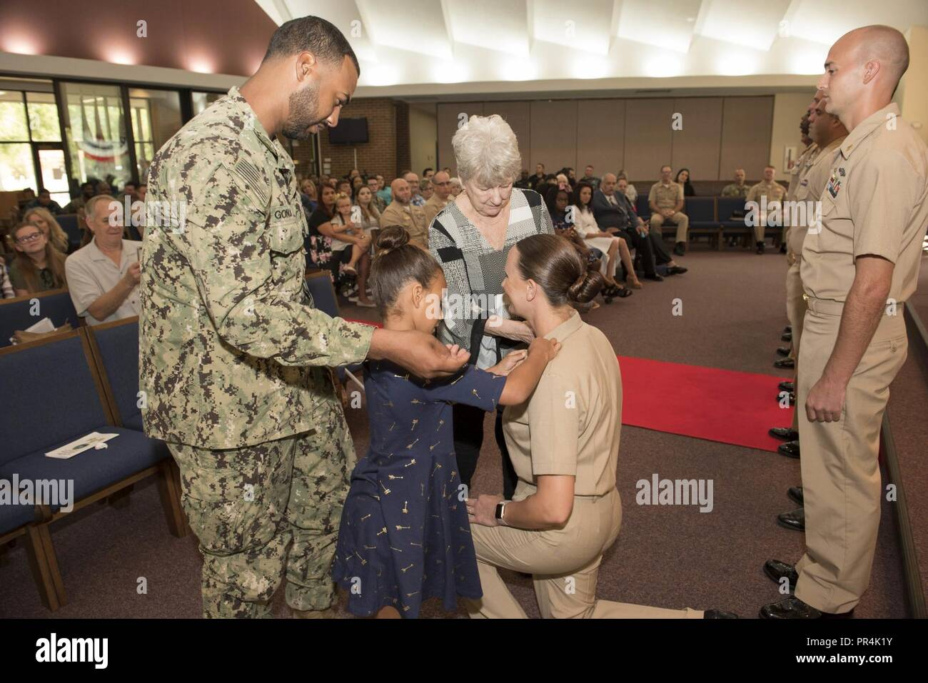 KINGS BAY, Georgia (Sept. 14, 2018) Chief Master at Arms Tara Gonga is pinned with her anchors by her family during Naval Submarine Base Kings Bay's 2018 chief petty officer pinning ceremony.  The base is home to six of the Ohio-class ballistic-missile submarines that make up the most survivable leg of the nuclear missile triad. - Stock Image