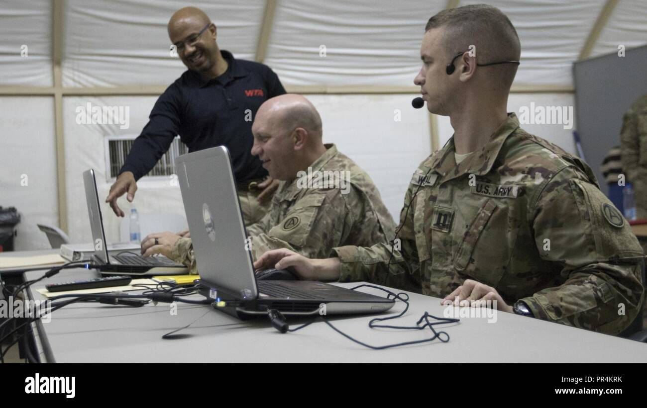 U.S. Army Capt. Jerry E. Thompson, middle, post chaplain for Camp Buehring, and U.S. Army Capt. Peter C. Wojtal, right, the incoming officer in charge of the U.S. Army Central Readiness Training Center, receive instructions on setting up voice recognition technology from Carey W. Menifee, an Intelligence and Electronic Warfare Tactical Proficiency Trainer operator and maintainer, before engaging in a suicide prevention virtual training exercise at Camp Buehring, Kuwait, Sept. 12, 2018. Suicide prevention is an enduring goal of the U.S. Army to ensure the safety and well-being of all Soldiers,  - Stock Image