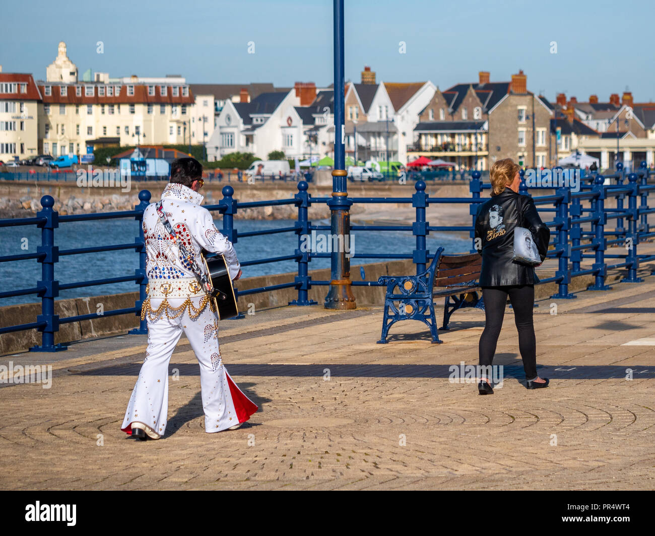 Porthcawl, UK. 29th September  2018. .Two fans heading along Porthcawl promenade towards the annual weekend-long Elvis Festival Credit: Paul Nicholas/Alamy Live News - Stock Image