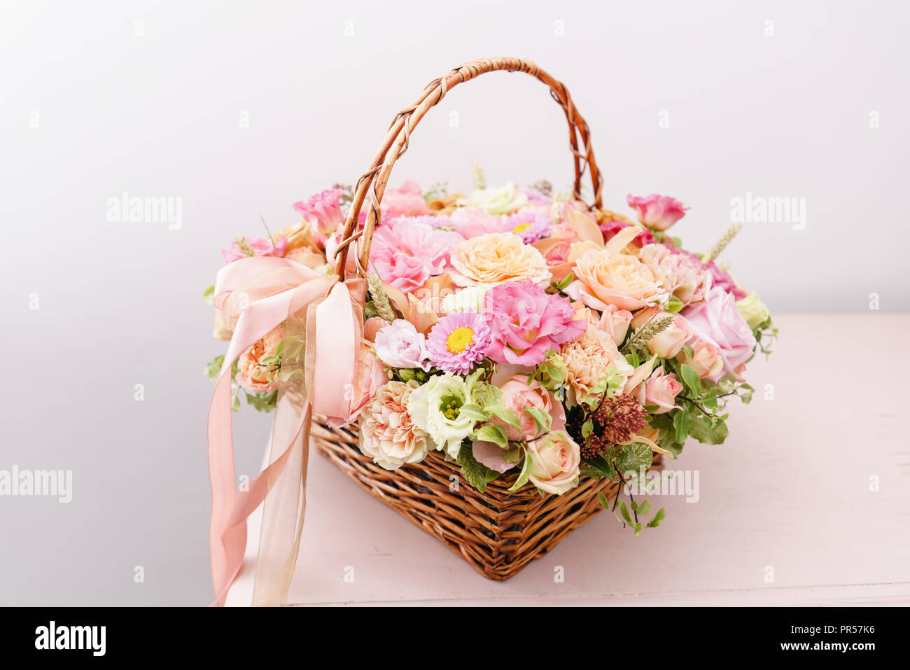Flowers Arrangement With Various Of Colors In Wicker Basket On Pink