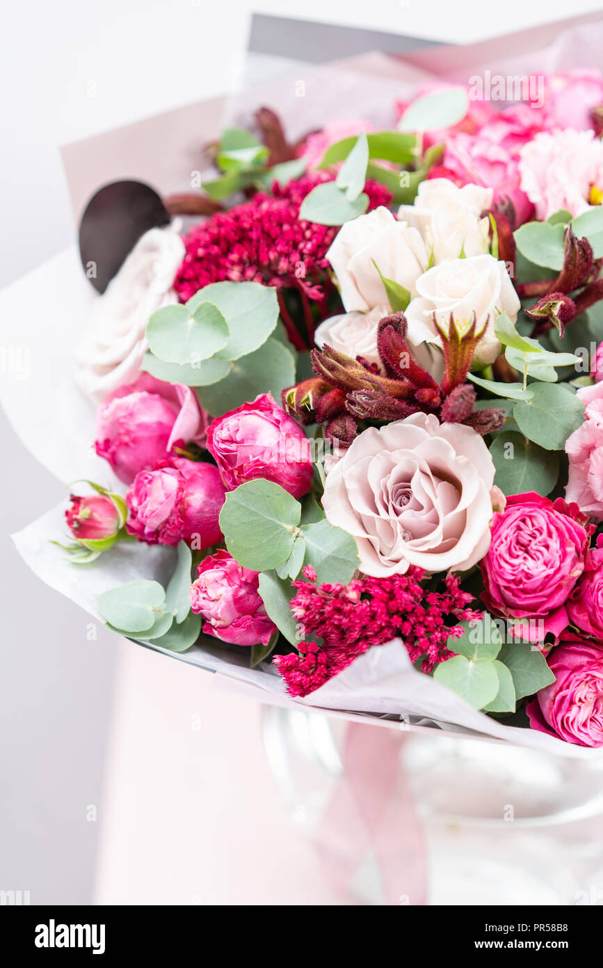 beautiful spring bouquet. flowers arrangement with various of colors in glass vase on pink table. bright room, white wall - Stock Image