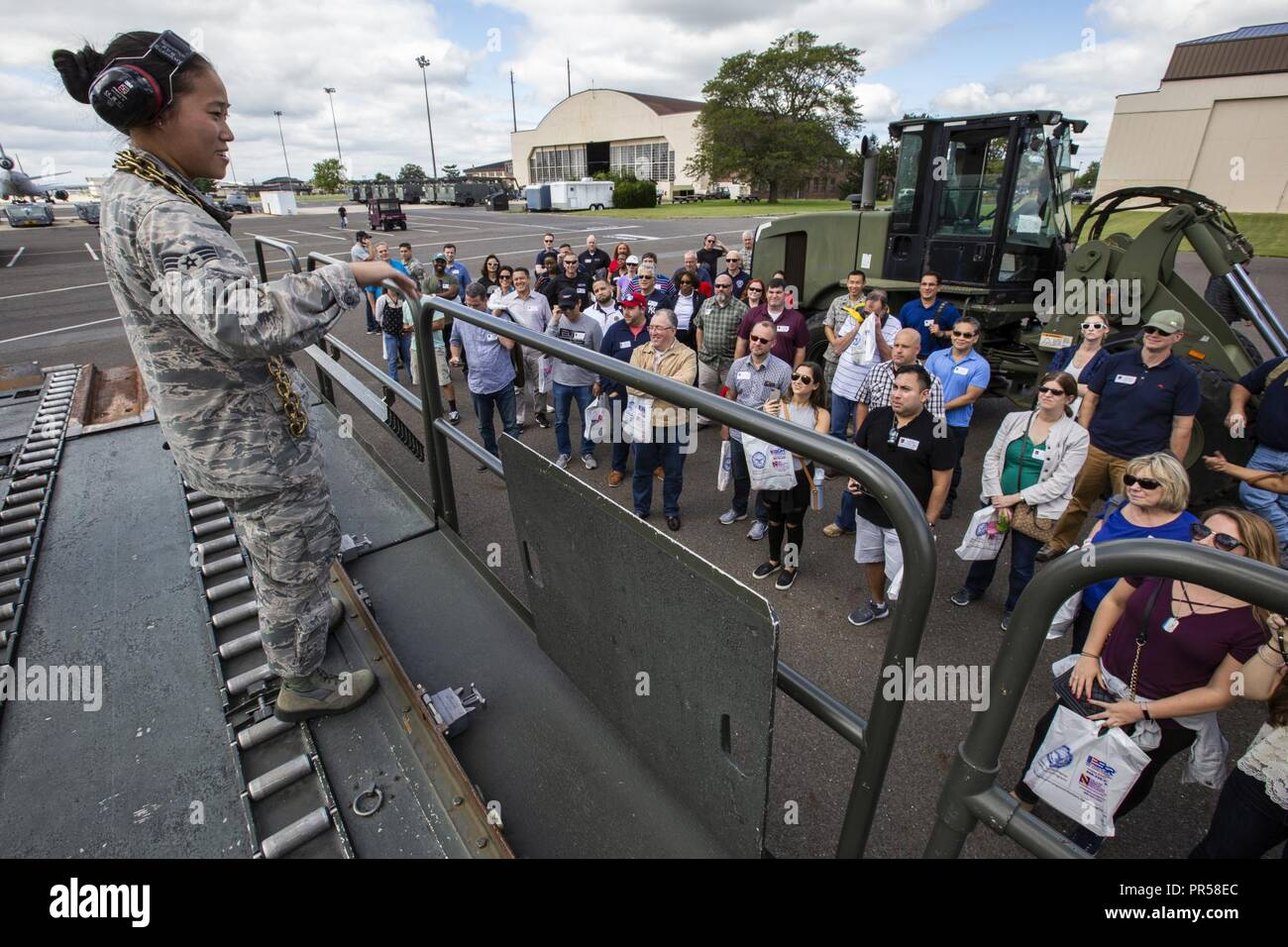 U.S. Air Force Senior Airman Vince N. Tsang, 88th Aerial Port Squadron, 514th Air Mobility Wing, discusses the capabilities of a Tunner 60K aircraft loader/transporter during the 514th Air Mobility Wing Employer Appreciation Day flight Sept. 15, 2018. The event, which included flying in a C-17 Globemaster III, was designed to show the employers what their employees do when they are serving with the 514th. The 514th is an Air Force Reserve Command Unit. - Stock Image