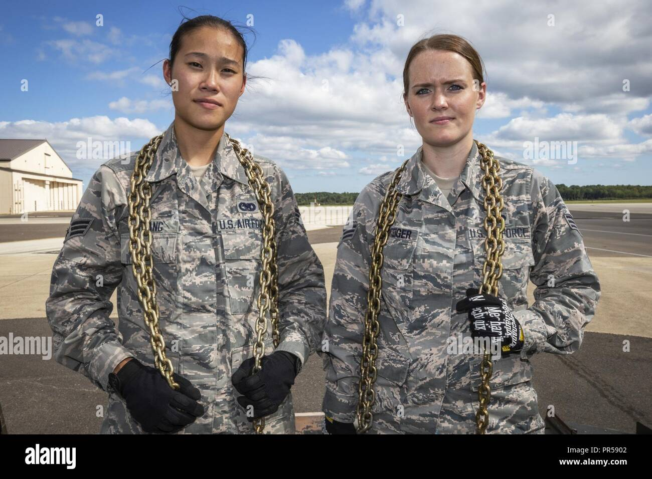 Portrait of U.S. Air Force Senior Airmen Vince Tsang, left, and Dannielle Potteiger, both with the 88th Aerial Port Squadron, 514th Air Mobility Wing, at Joint Base McGuire-Dix-Lakehurst, N.J., Sept. 15, 2018. The 514th is an Air Force Reserve Command Unit. - Stock Image