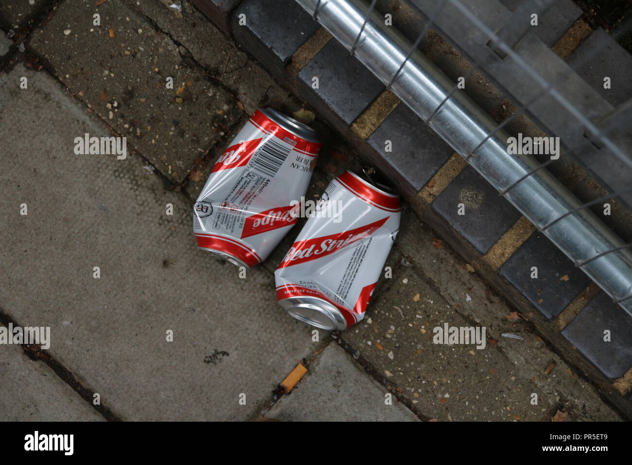 London, UK - August 27, 2018: Red stripes beer cans after party morning - Stock Image