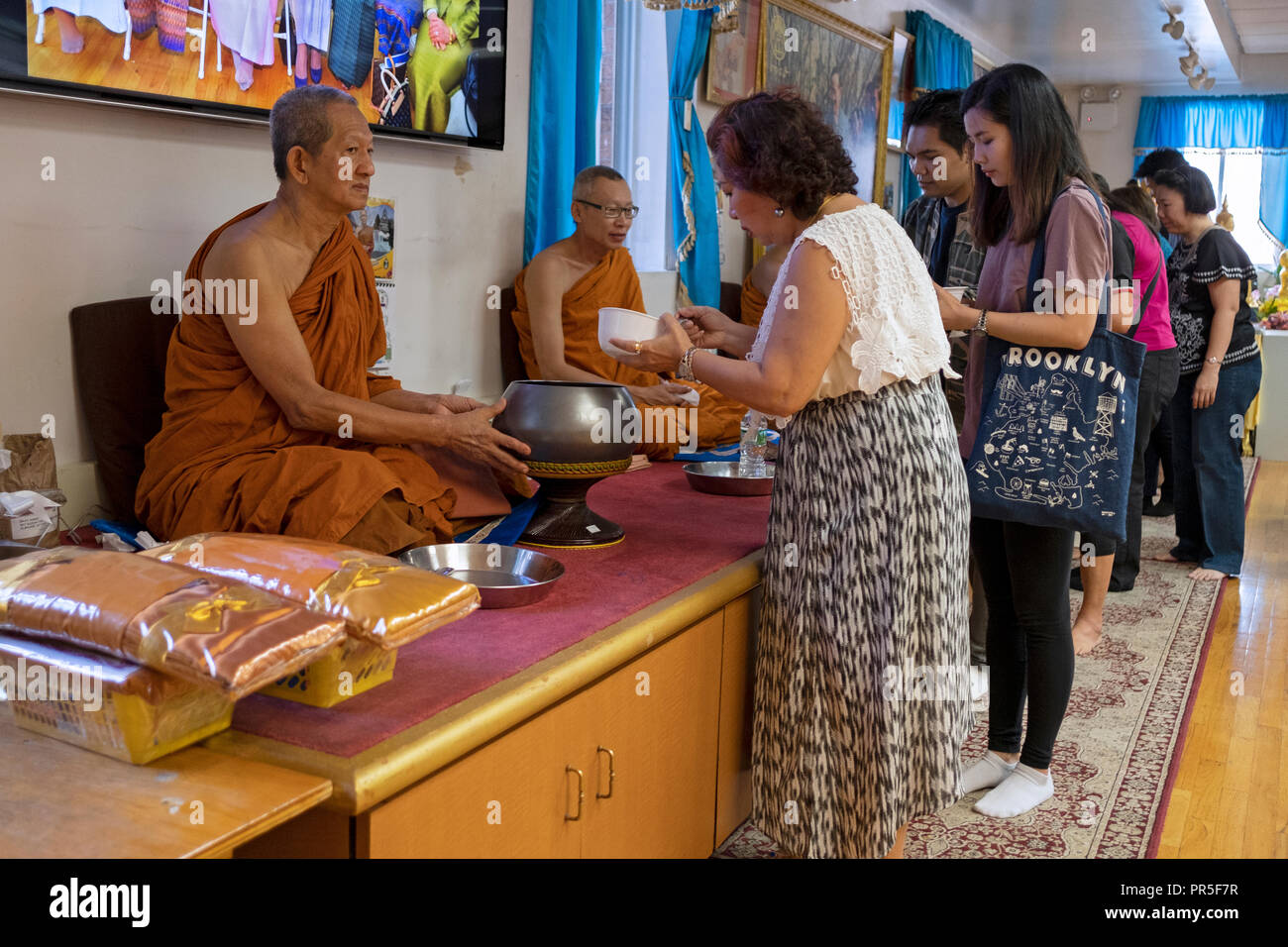 Worshipers at a Buddhist temple participate in the tradition where the congregation feeding the monks. In Queens New York City. - Stock Image