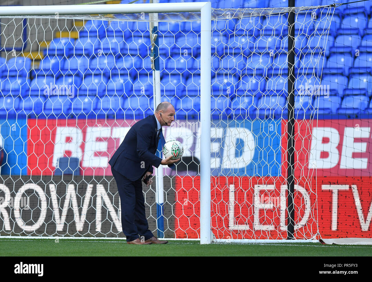 The match official checks the goal line technology before the Sky Bet Championship match at the University of Bolton Stadium. - Stock Image