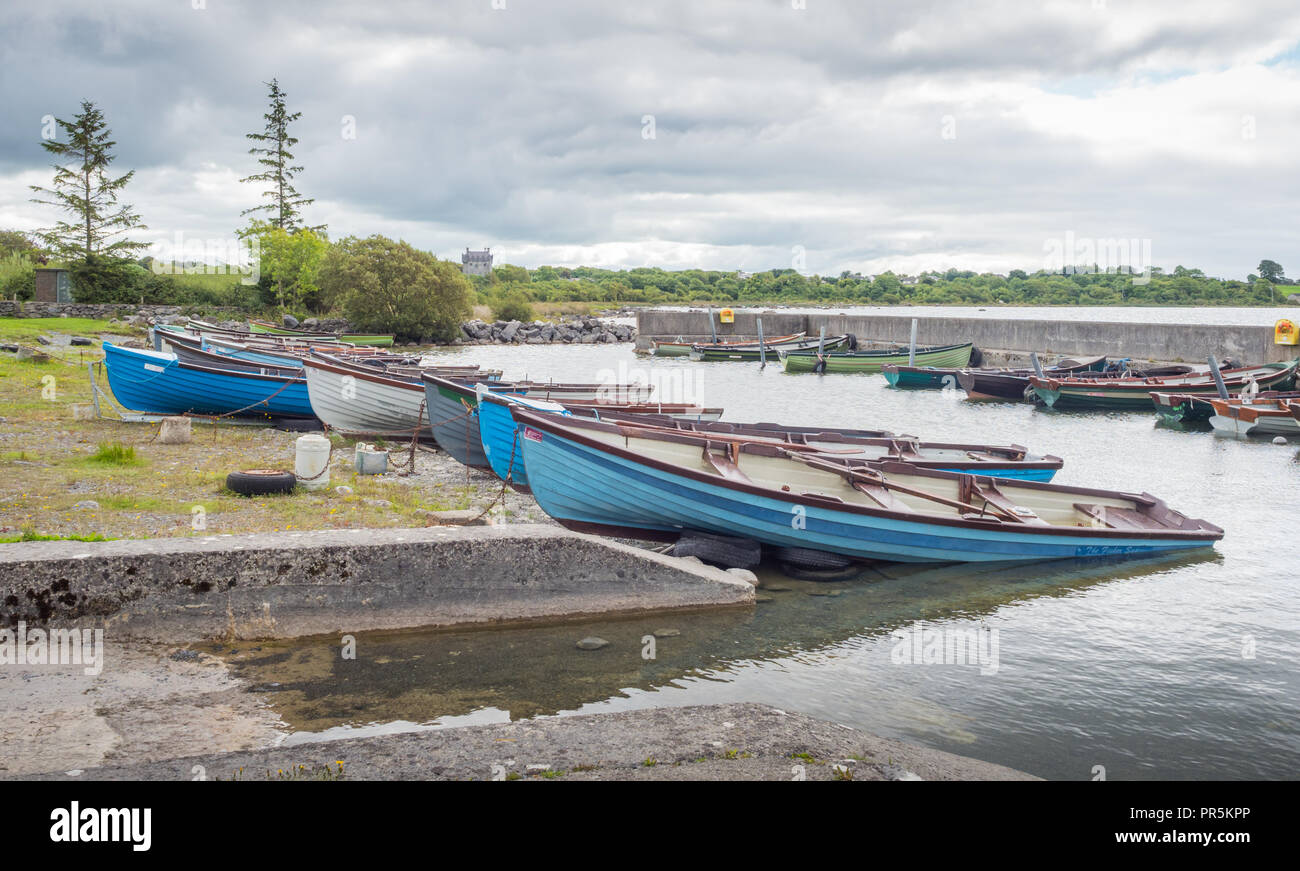 Rowing boats lined up at Annaghdown Pier in County Galway in Ireland. Stock Photo