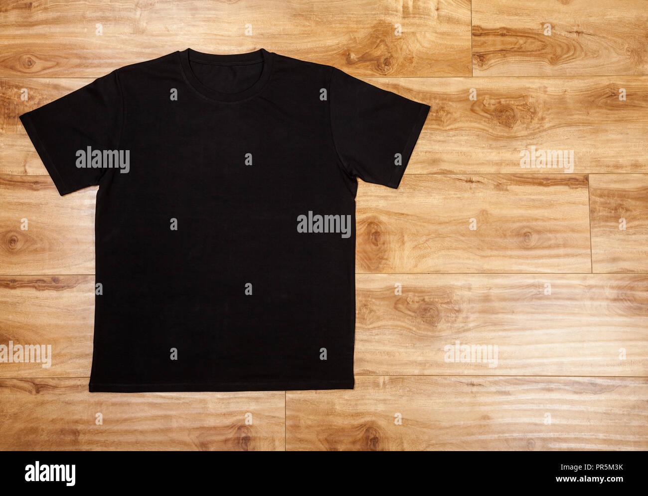 Black plain short sleeved cotton T-Shirt on a planket wooden background - Stock Image