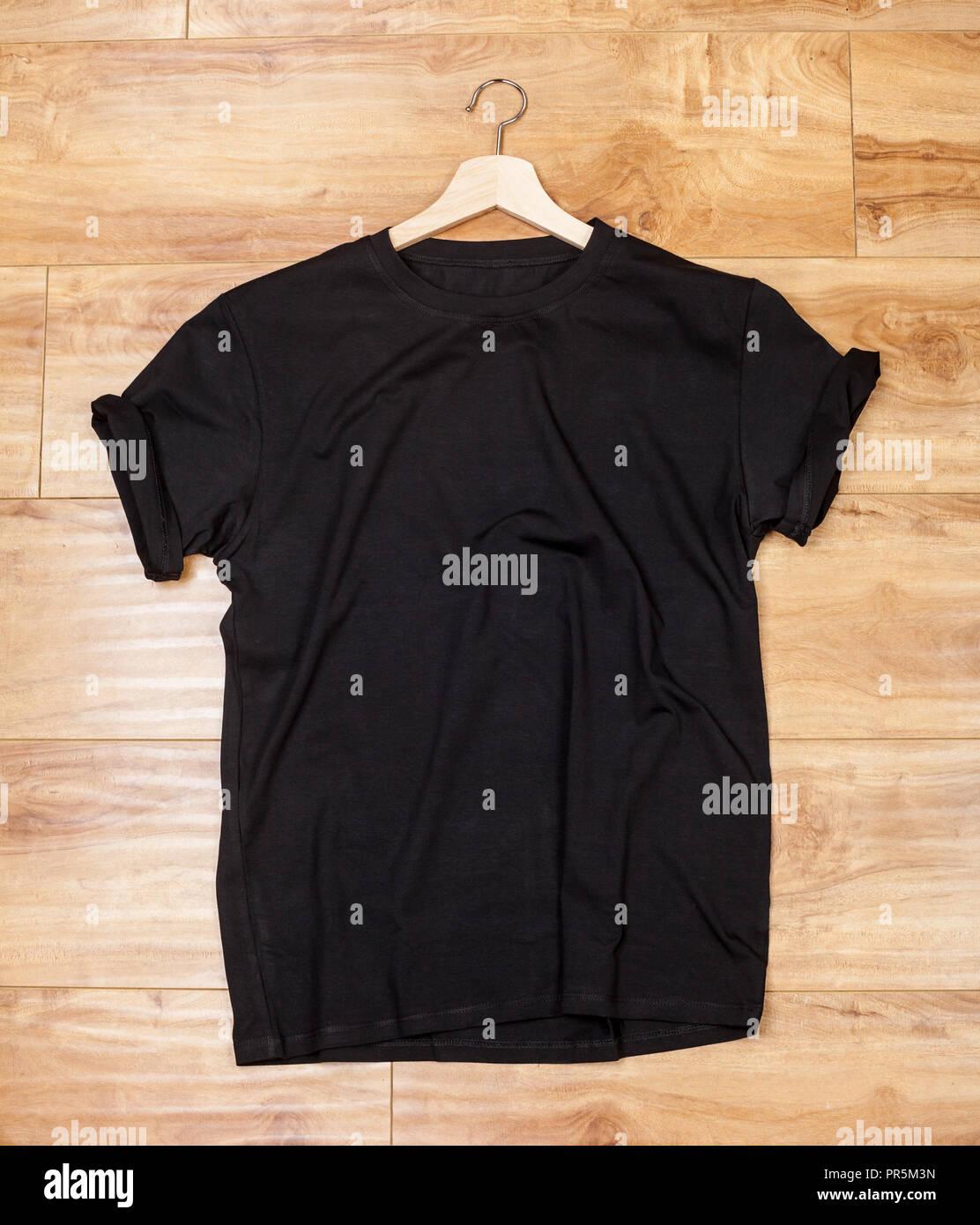 Wrinkled black plain short sleeved cotton T-Shirt on a planket wooden background - Stock Image