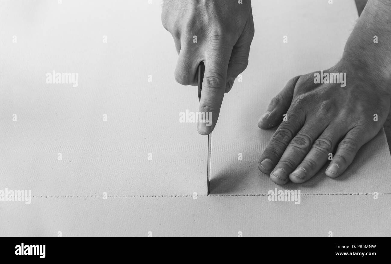 man cuts a sheet of heat insulating and sound proof material with a stationery knife, black and white photo - Stock Image
