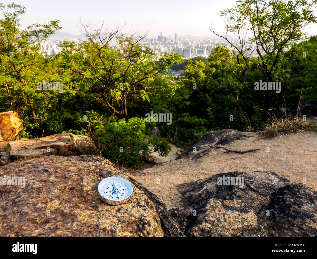 Reliable compass on stone in Seoul, South Korea. Concept for travelling and active lifestyle. - Stock Image