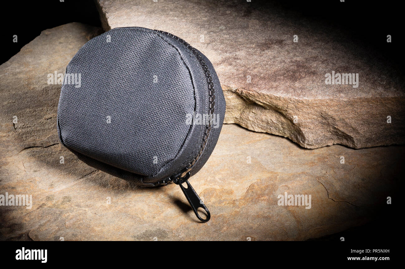 Tactical pouch to hold gear on several large piece of rock - Stock Image