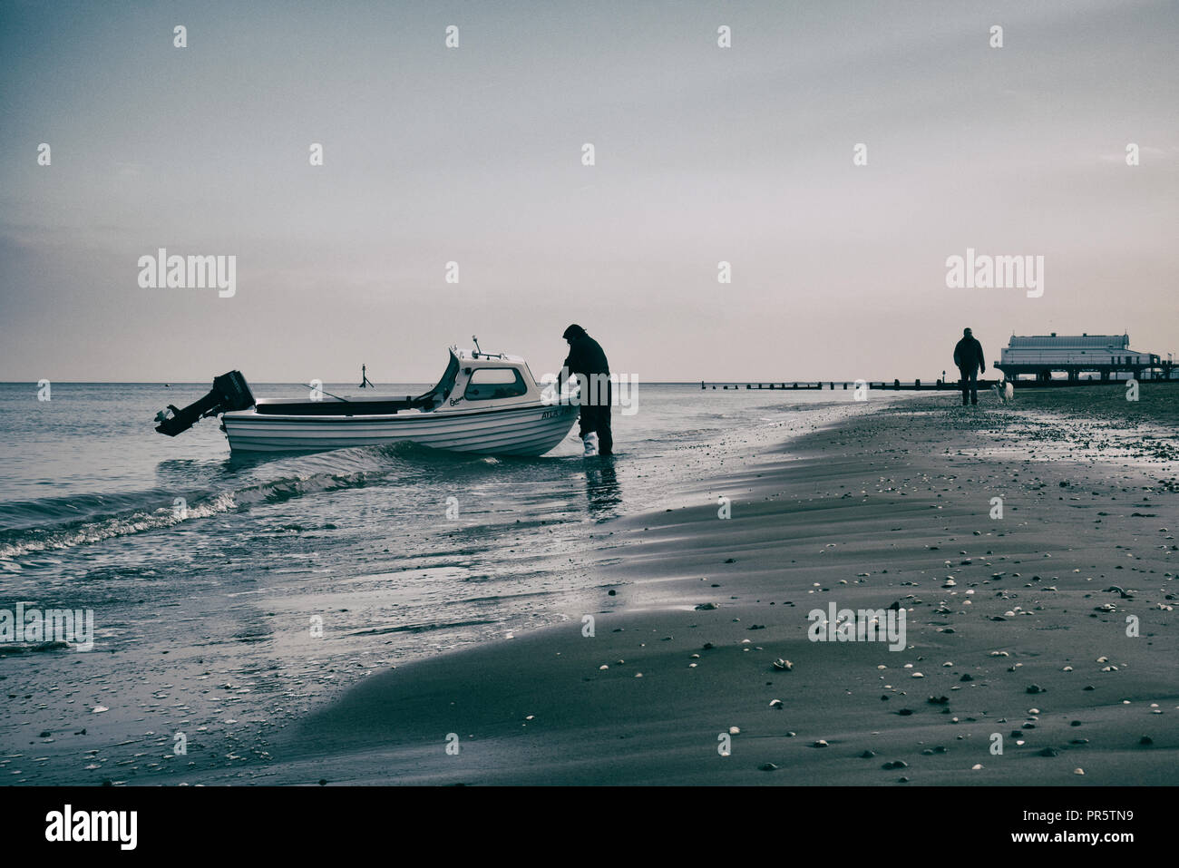Small fishing boat coming ashore at Cleethorpes - Stock Image