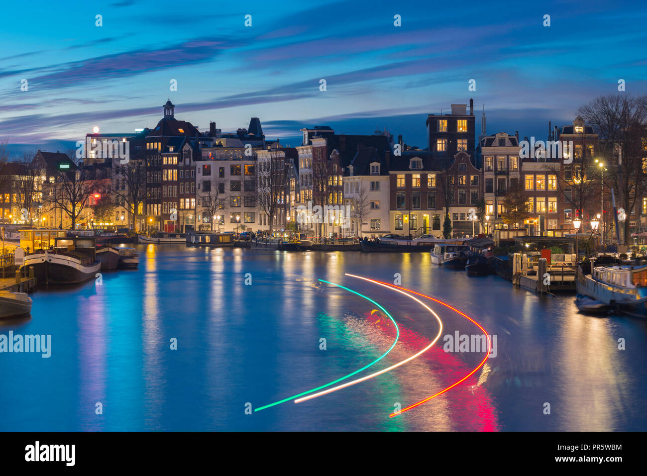 Beautiful Amsterdam canal with light trails of passing canal boat. Stock Photo