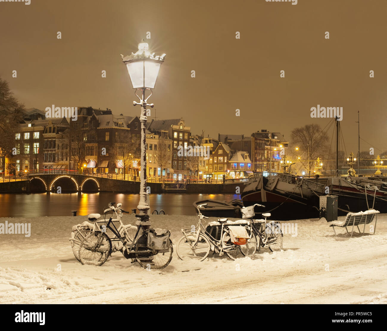 Amsterdam with snow and parked bicycles. A beautiful, typical Dutch  winter scene. Stock Photo