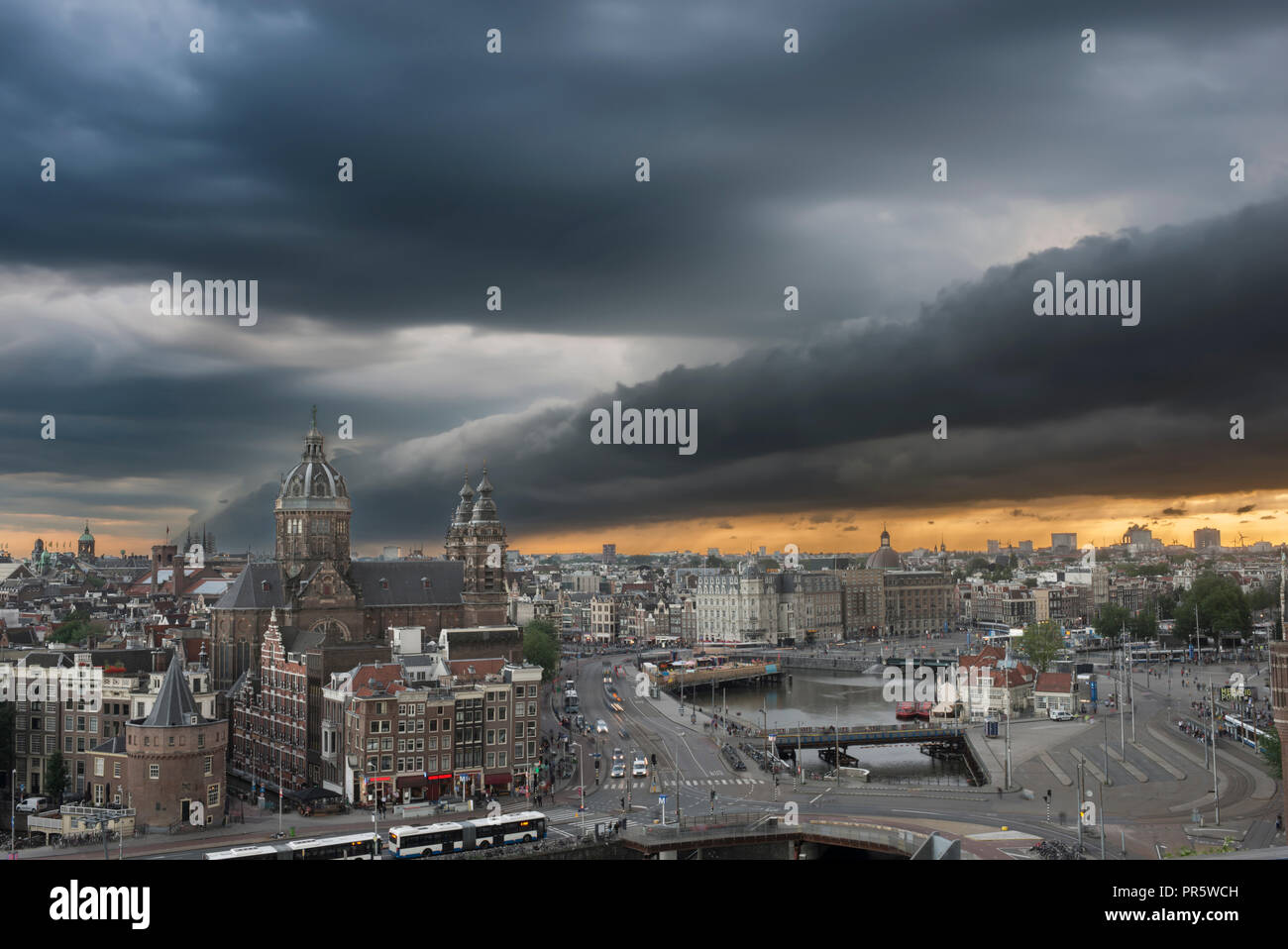 Spectacular tube-shaped roll cloud above the centre of Amsterdam, The Netherlands, with basilica St. Nicolaas. - Stock Image