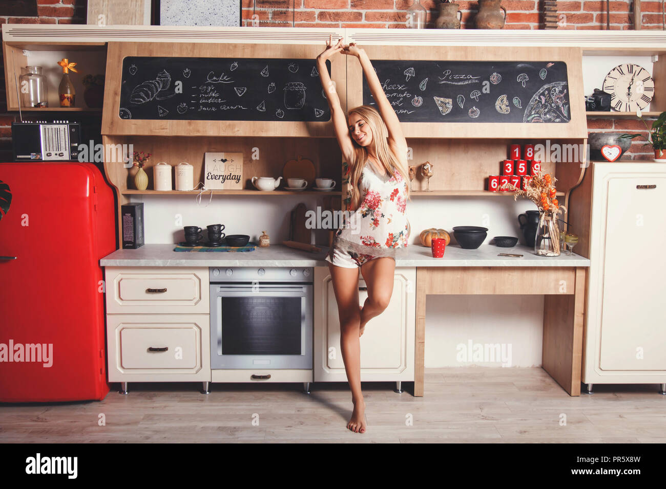 Cute blonde long hair girl wearing sleapwear standing in the red loft comfortable sunny kitchen, stretching oneself and preparing to the new day - Stock Image