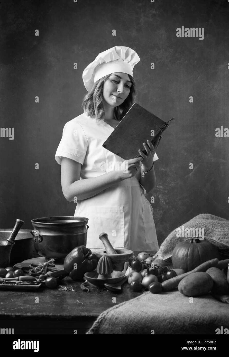 Young beautiful girl in a chef's uniform reads an old cookbook. On the table, different kitchen utensils and vegetables. - Stock Image