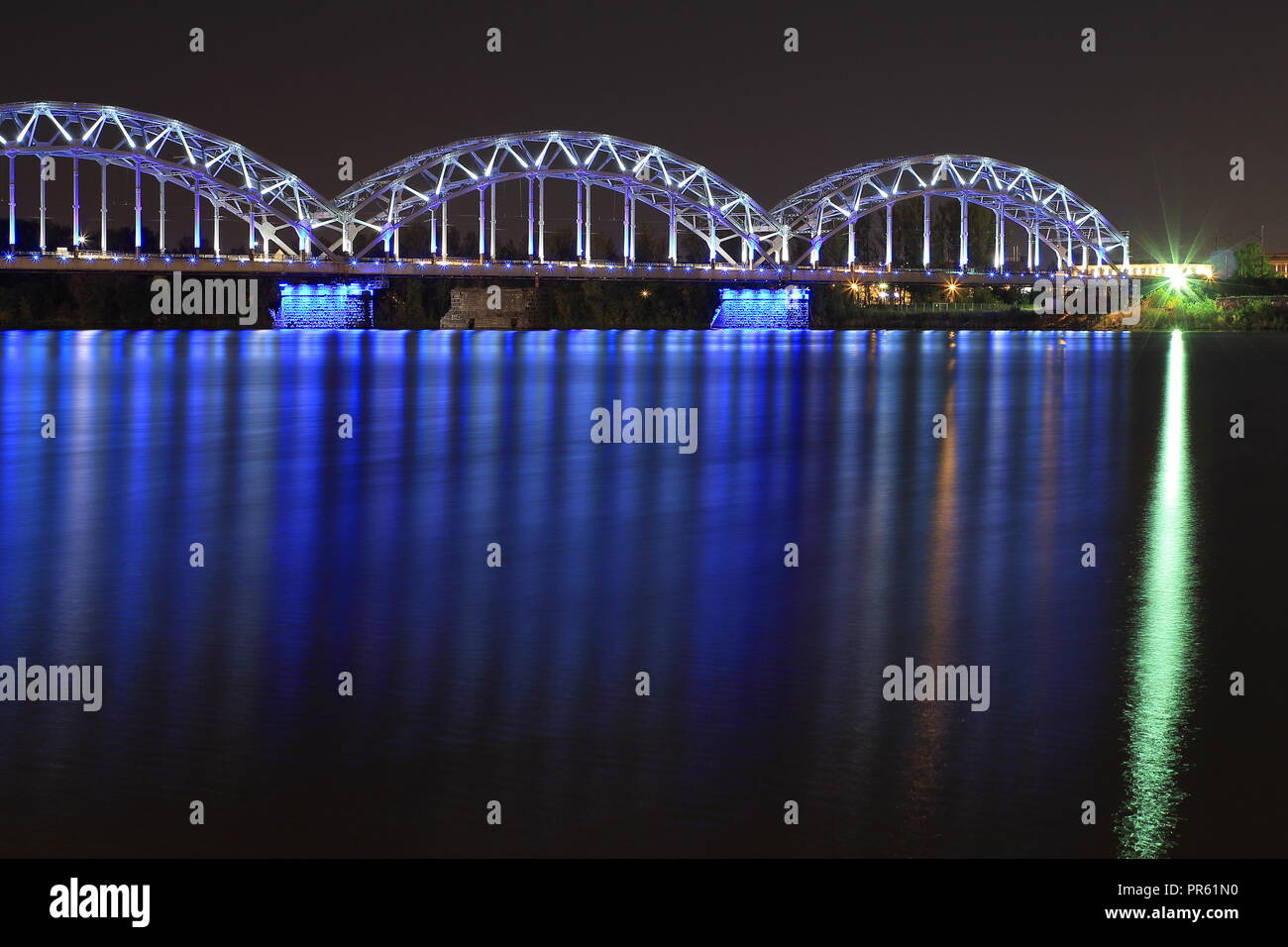 Railway Bridge crosses the Daugava river in Riga ( Latvia ) at night. Latvians celebrates its 100 years of independence throughout the year 2018. - Stock Image