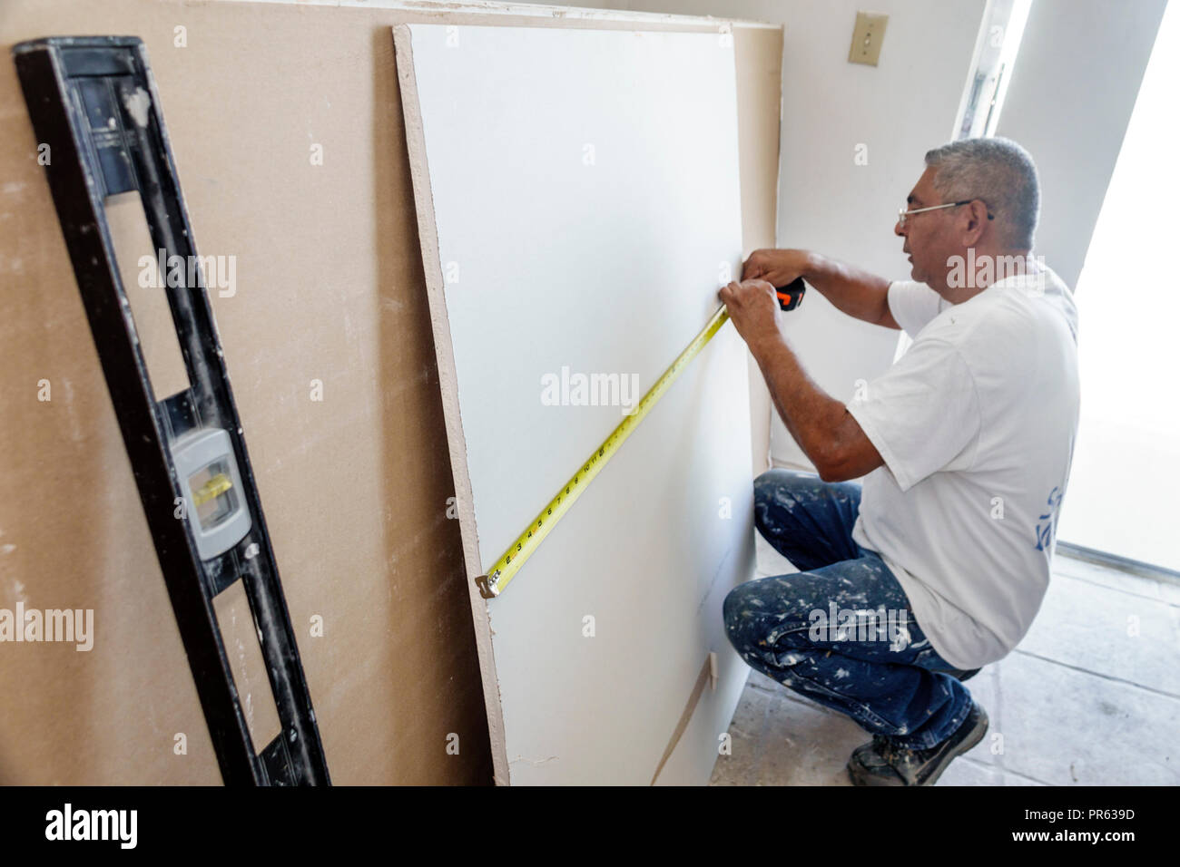 Miami Beach Florida contractor renovation repair drywall Hispanic man measuring tape measure cutting working - Stock Image