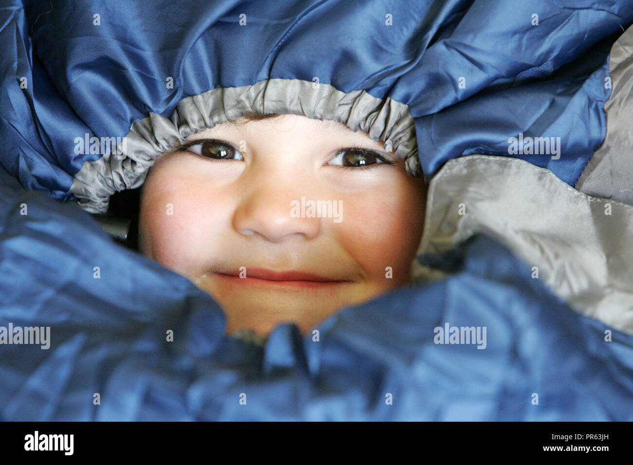 Young boy snug in a sleeping bag - Stock Image