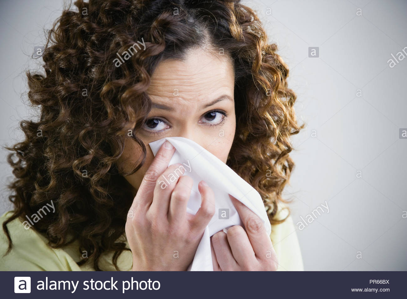 Close up of woman dabbing eye with tissue - Stock Image