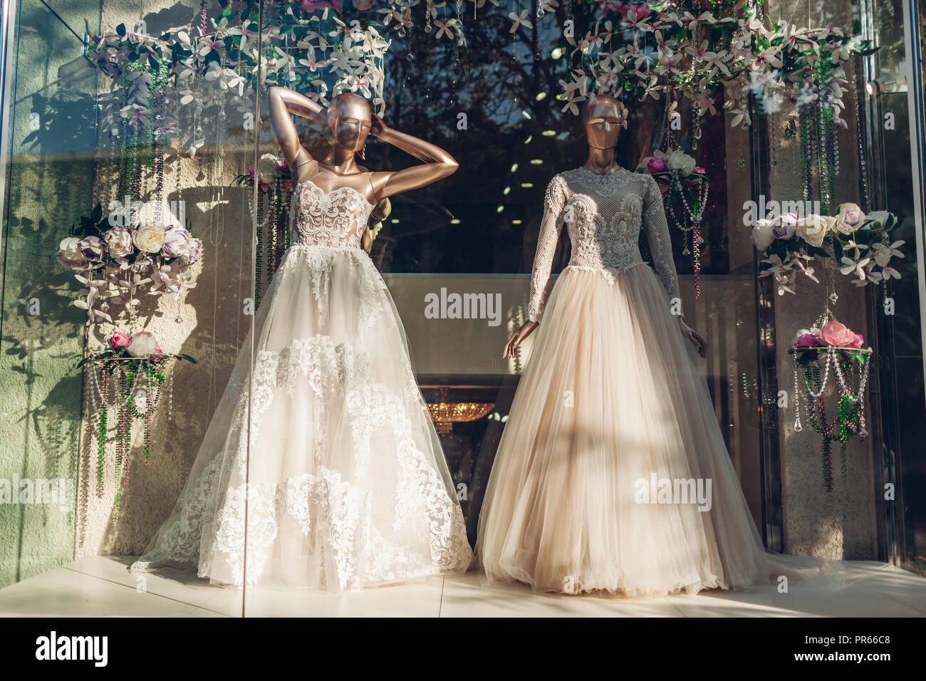 27c6daeb4 Collection of stylish wedding dresses on showcase of shop. Two mannequins  wearing beautiful gowns on