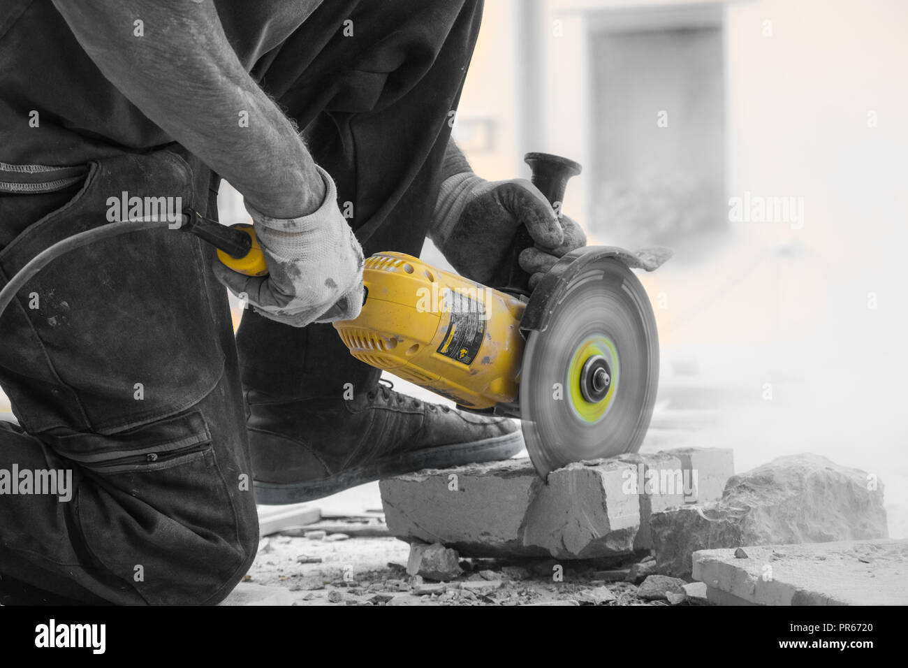 Worker cutting limestone block with power tool saw - Stock Image