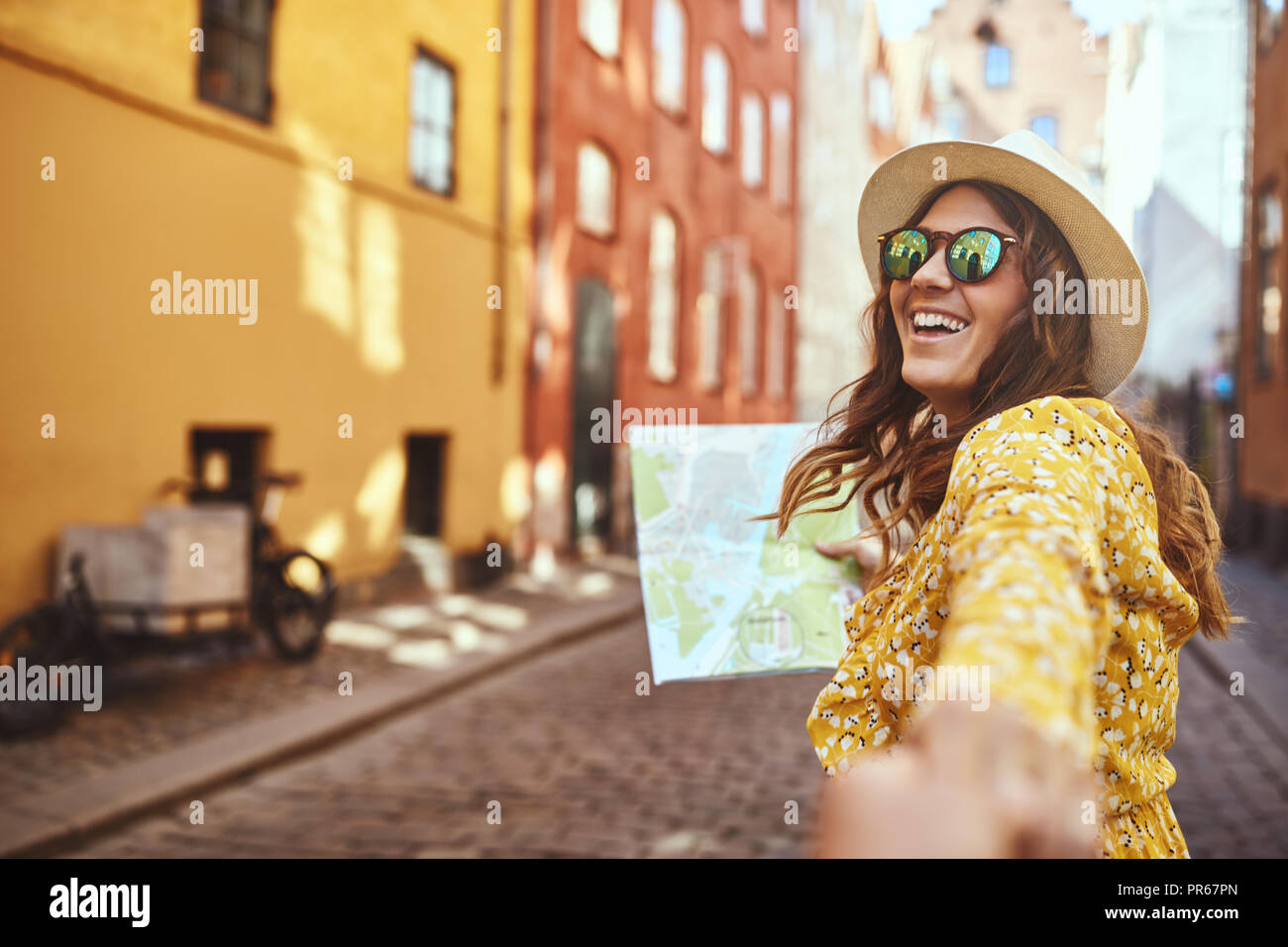 POV of a smiling young woman wearing sunglasses and holding a map leading another person by the hand while exploring city streets together - Stock Image