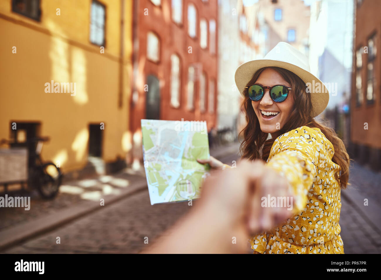 POV of a smiling young woman holding a map and wearing sunglasses leading another person by the hand while exploring city streets together - Stock Image