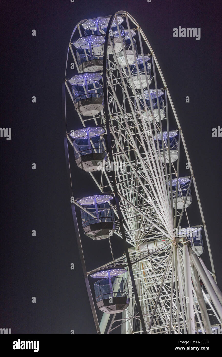 a large fairground ferris or big wheel ride illuminated and lit with lights against the night sky - Stock Image
