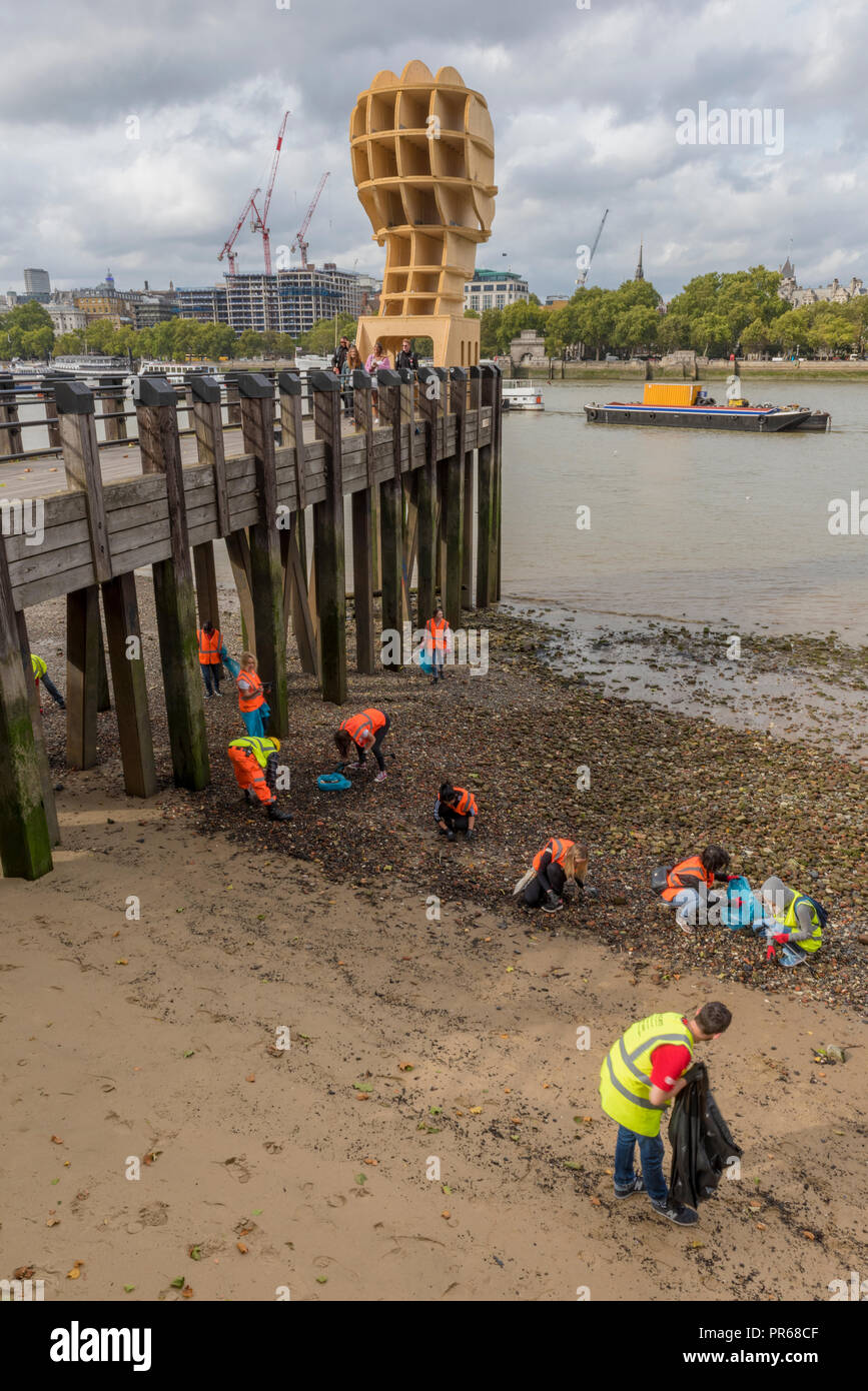 beach clean taking place with volunteers wearing high visibility clothes on the foreshore of the river thames in central london. - Stock Image