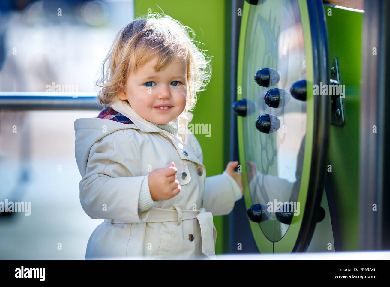 Sweet blond little baby girl in hooded trench coat plays outdoors at playground - Stock Image
