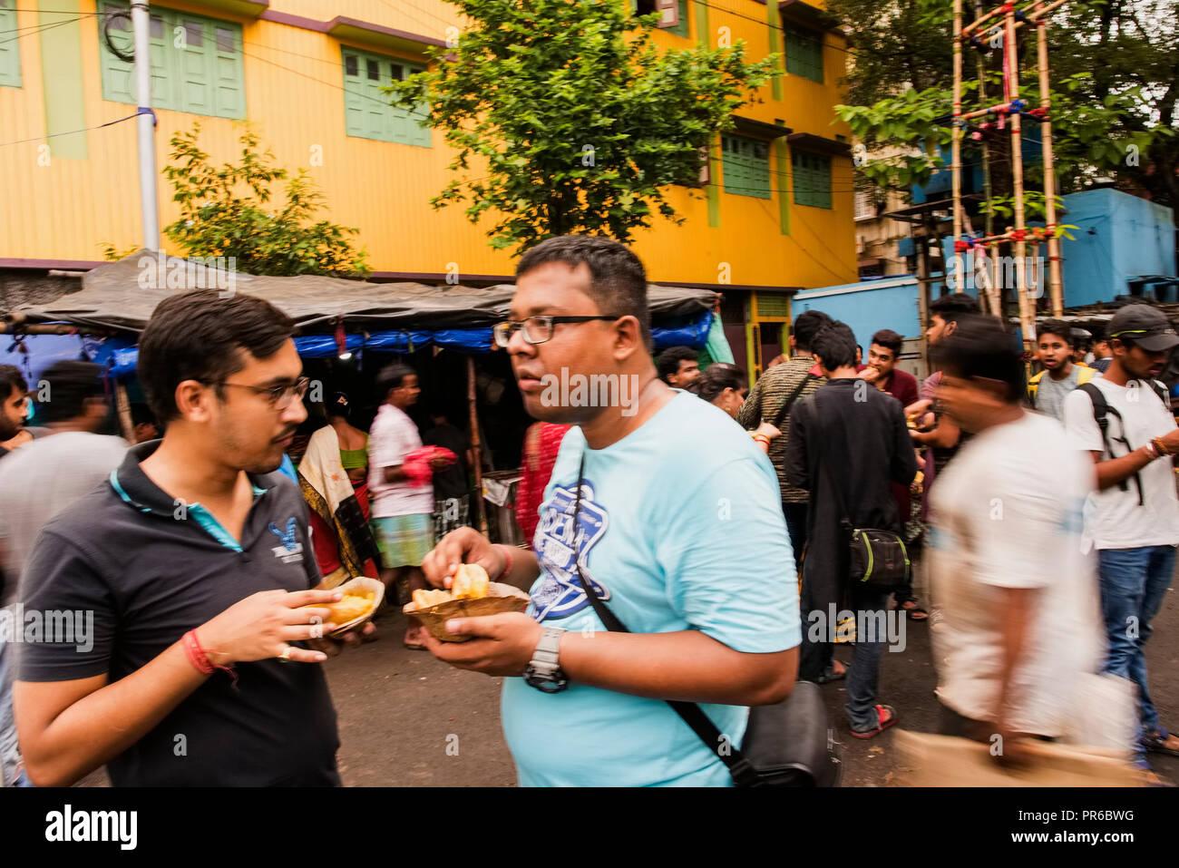 Two young ,Durga Puja,organisers,enjoying street food,at Kumartuli,Kolkata,clay idol makers,hub,India. - Stock Image