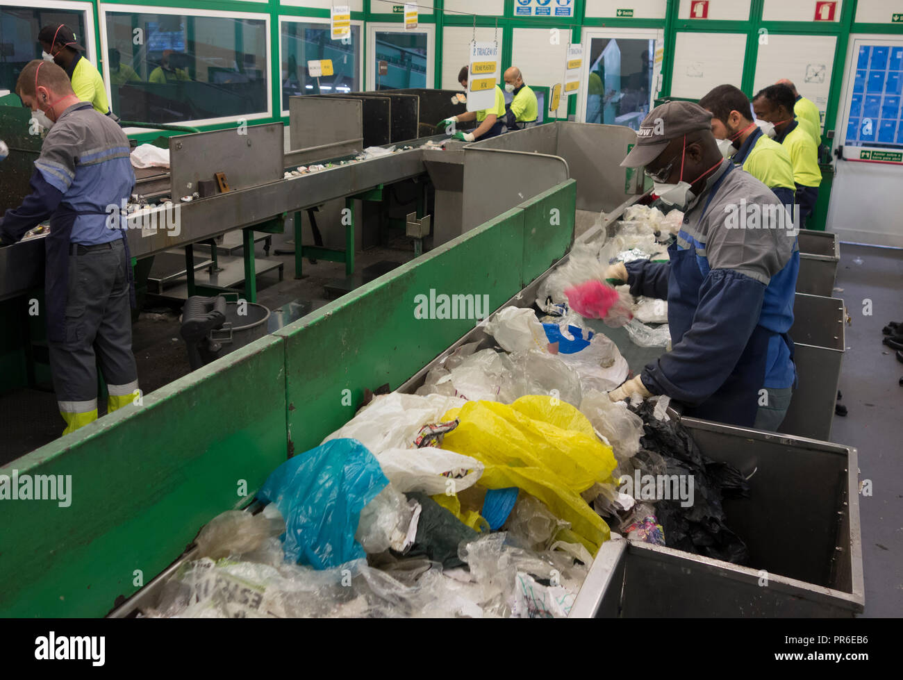 Employees of a waste facility on a conveyor belt sorting line. Manual sorting of plastic to to separate non-recyclable plastic PET objects. Some - Stock Image