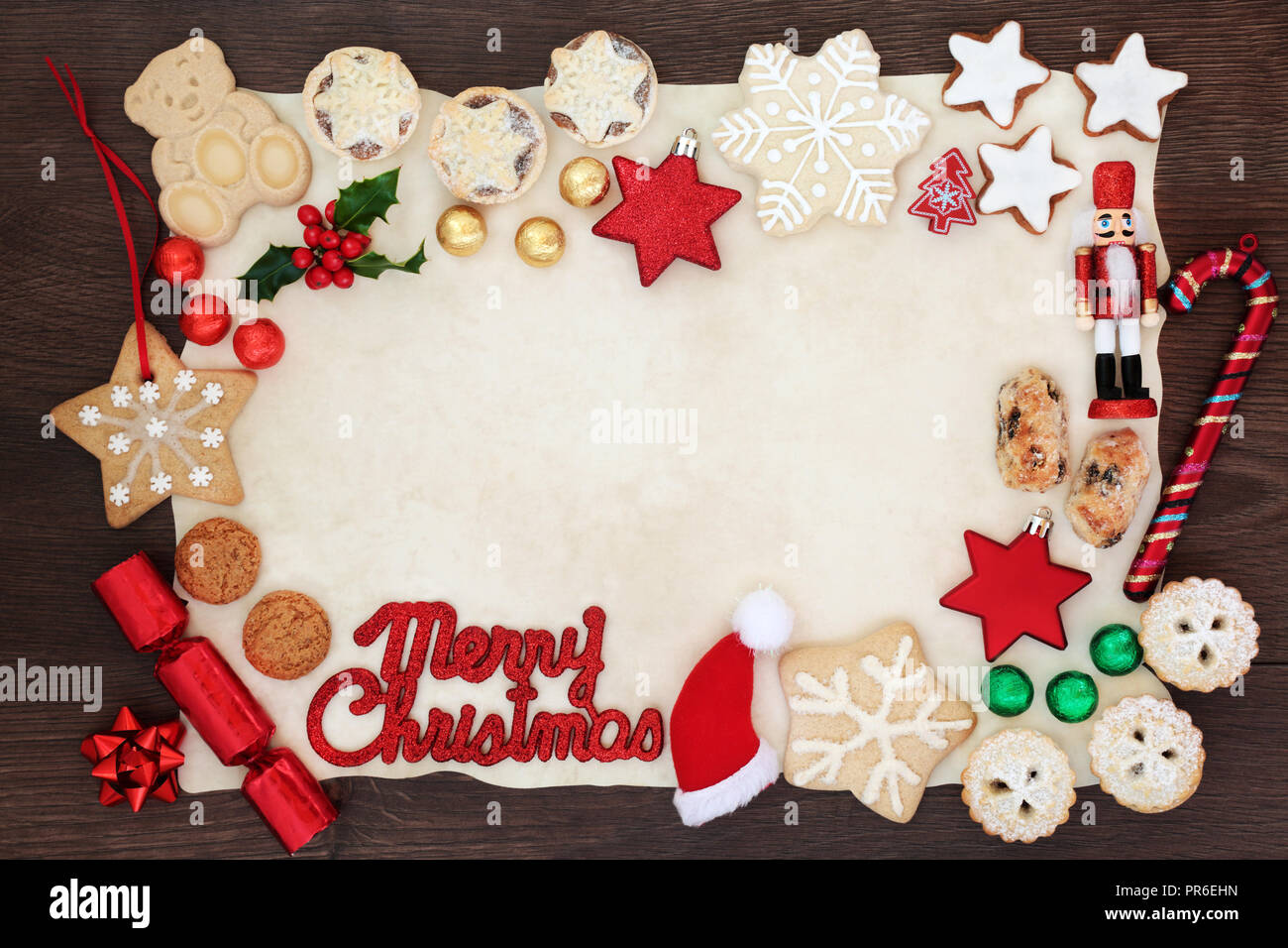 Merry Christmas background border with sign, tree decorations, biscuits, cakes, winter flora  and chocolates in foil on parchment paper on rustic wood - Stock Image