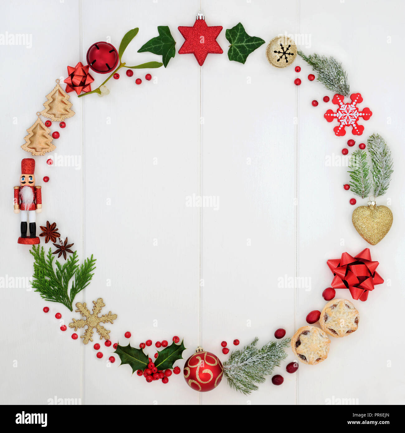 Abstract Christmas wreath garland with a selection of traditional symbols including food, flora and bauble decorations on rustic white wood background - Stock Image