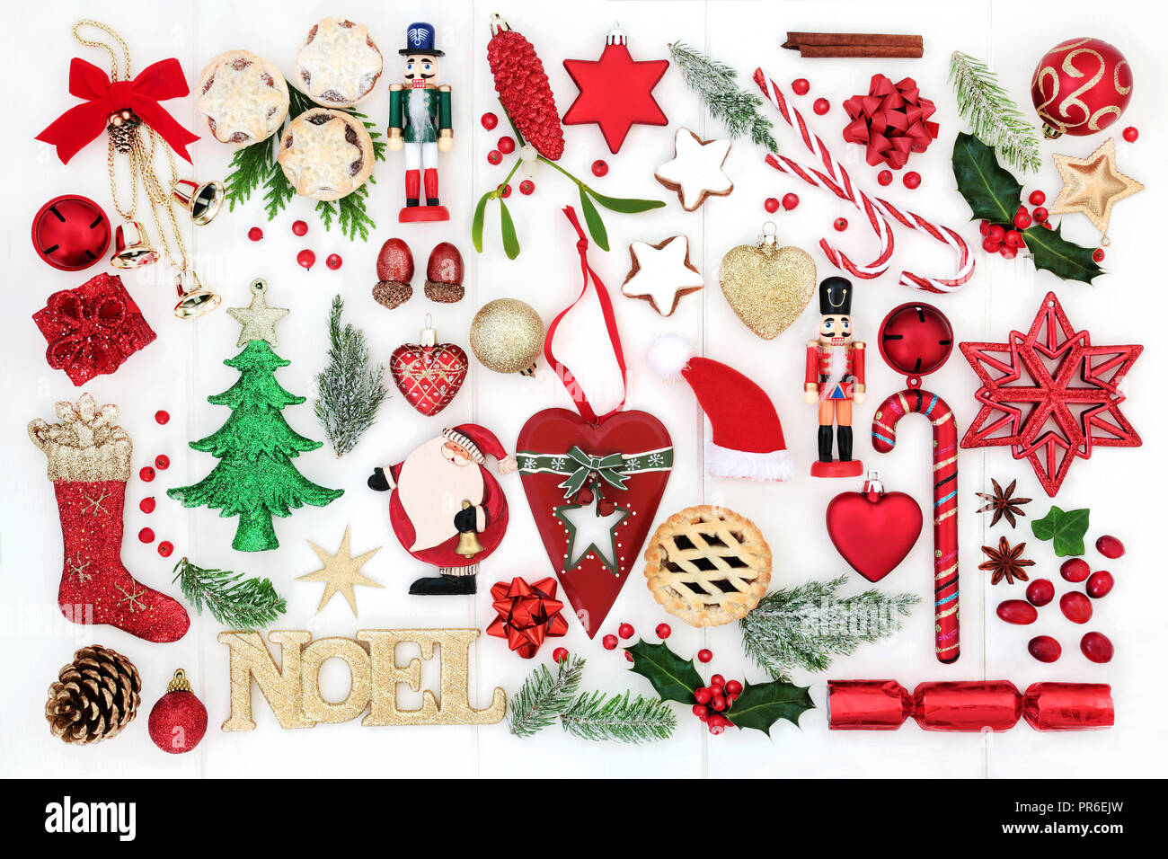 Christmas background with noel sign, retro and new bauble decorations, candy canes, mince pies, winter flora,  ribbons and bows on rustic white wood.  - Stock Image