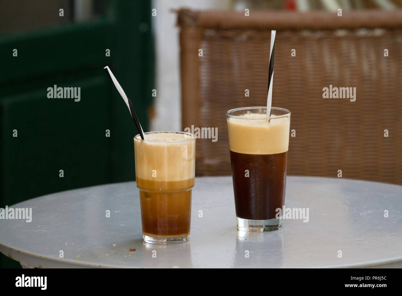 Coffees in glasses, with straws, waiting to be drunk - Stock Image