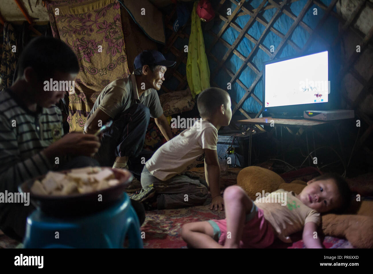 A general view from a local family watching TV inside a yurt after finishing their dinner near the town of Tsogt-Ovoo in Ömnögovi Province in southern Mongolia. - Stock Image