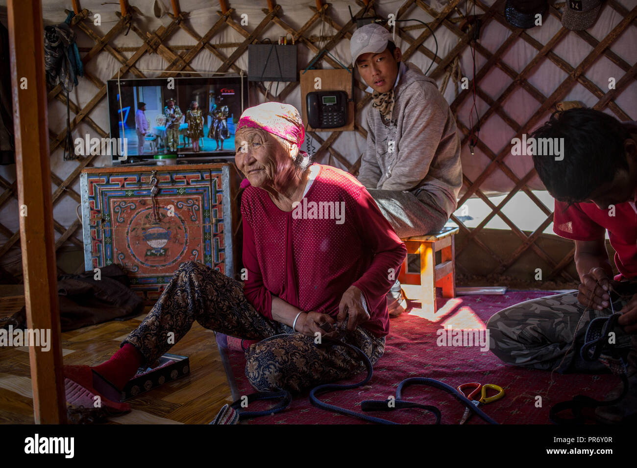 An old woman seen sewing homemade camel's muzzles for the